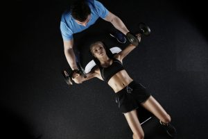 woman training arms with fitness trainer