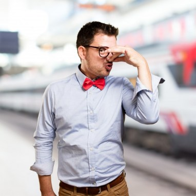 man-wearing-red-bow-tie-doing-bad-smell-gesture
