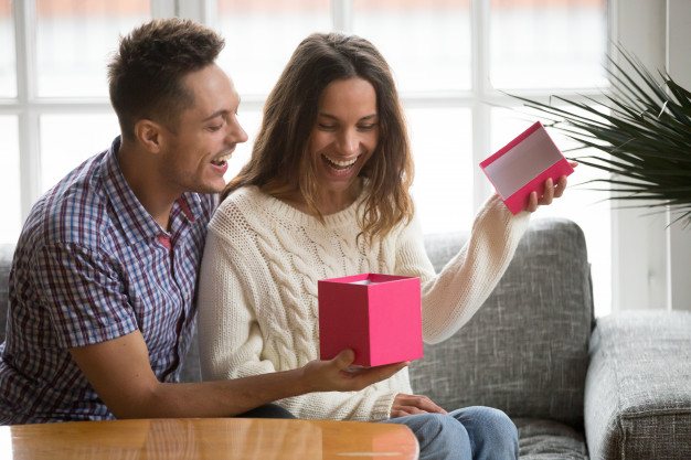 Guy surprising girl with a gift