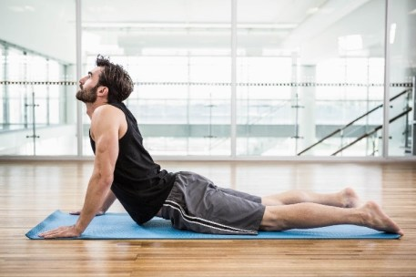healthy man doing cobra stretch exercise