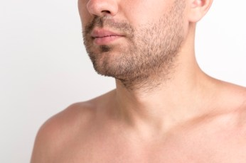 close-up-shirtless-stubble-beard-man-against-white-background