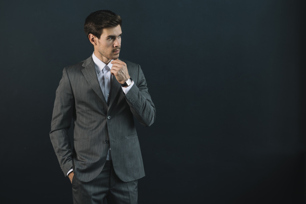 contemplated-young-businessman-against-black-background