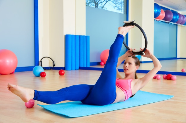 very slim woman doing exercise pilate ring