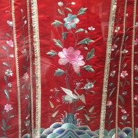 Detail from the embroidered red silk skirt of a lady from the late Qing dynasty (c1900), currently on display at the Silk Museum as part of their exhibition celebrating 25 years of acquisitions