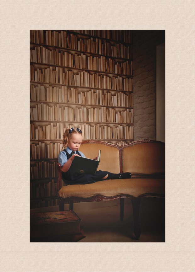 Girl sitting on vintage seat reading a book in school uniform