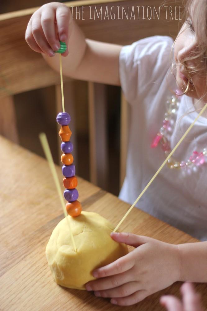 Threading-with-beads-on-spaghetti-666x1000