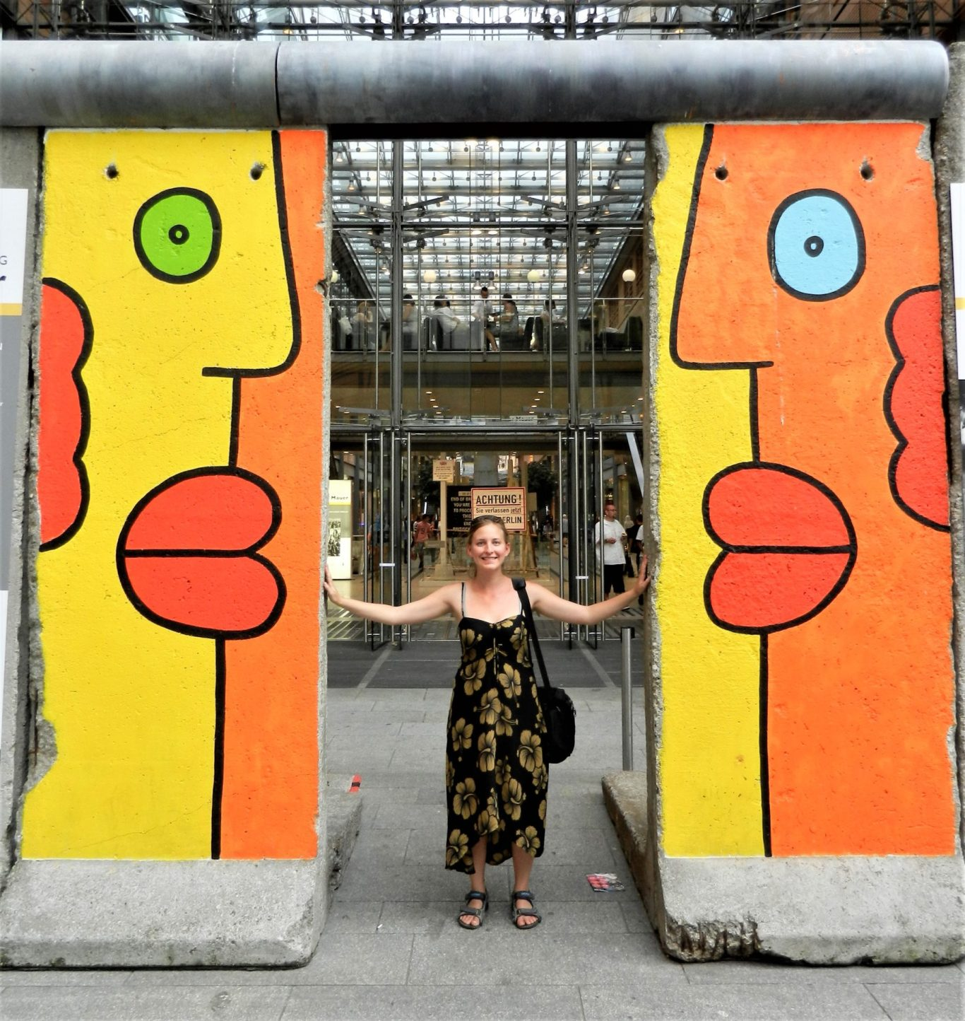 Ashleigh between two Berlin wall segments in Berlin, Germany