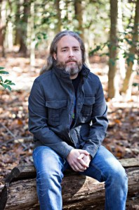 The author sits outside on a log in a wooded area wearing a dark blue jacket and blue jeans.