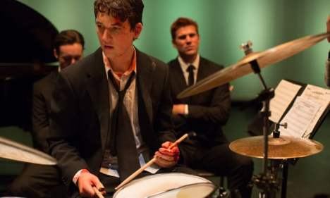 3 boys sitting in a room and a drummer with drum sticks in his hands