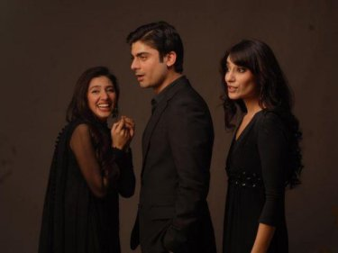 two women laughing and standing on either side of a man, all dressed in black