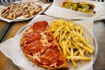 in image plates with pizza and fries kept on a table