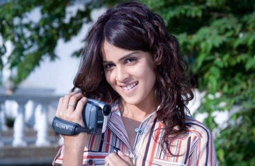 a girl smiling and blushing holding a video camera in her hand