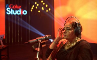 an old woman sitting and adjusting her headphones singing on the mic