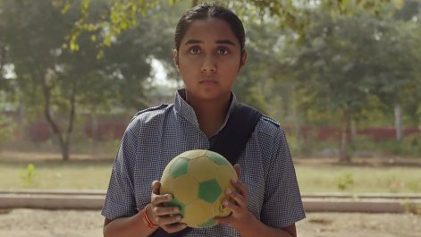a girl in school uniform holding a throwball