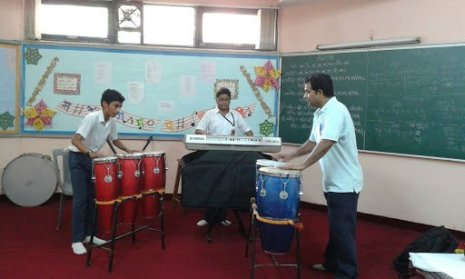 few children playing bongos in the school music room