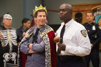a scene from Brooklyn nine nine of halloween heist with jake weaing a crown and hot wearing a patch for filmy firendships