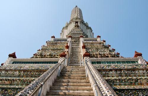 Il Wat Arun (thailandese: ???????, Tempio dell'Alba) e un tempio buddhista (wat) a Bangkok, Thailandia. Il tempio si trova nel distretto del Bangkok Yai, sulla riva sinistra del fiume Chao Phraya. Il nome completo del tempio e Wat Arunratchawararam Ratchaworamahavihara (?????????????????????????????). La piu notevole caratteristica del Wat Arun e la sua guglia istoriata (prang) centrale, simile alle torri che e possibile trovare in altri importanti templi khmer. Una serie di ripidi gradini portano alle due terrazze, la cui altezza, secondo alcune rilevazioni, sarebbe di 66,80 e 86 m. Gli angoli della struttura sono sormontati da 4 prang piu piccoli, decorati, come il prang principale, da conchiglie e cocci di porcellana, precedentemente usati come zavorra dalle imbarcazioni in arrivo a Bangkok dalla Cina. Attorno alla base dei prang e possibile vedere figure di antichi soldati cinesi, e di animali. Sopra la seconda terrazza sono presenti quattro statue del dio indu Indra, che cavalca l'elefante mitologico Erawan. Sul lato che guarda il fiume, sono presenti 6 padiglioni (sala) in stile cinese, costruiti con granito verde e attrezzati con ponti levatoi. Non lontano dai prang e possibile trovare la Sala dell'Ordinazione, con l'immagine del Buddha Niramitr, che si dice sia stato progettato dal re Rama II del Siam (inizio XIX secolo). L'entrata principale della Sala e sormontata da un soffitto dal quale e possibile vedere l'interno di una delle guglie, decorate con ceramiche e stucchi, a loro volta colorati con chine di diversi colori. Tra i soggetti raffigurati, due demoni, uno bianco e uno verde, sono ben visibili di fronte a chi entra. http://it.wikipedia.org/wiki/Wat_Arun