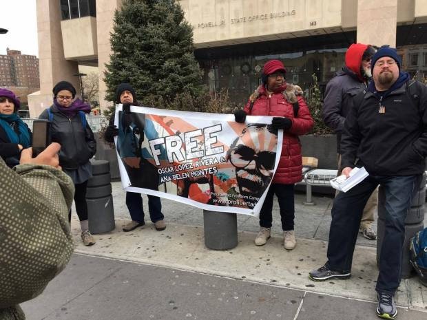 Activists hold up a banner for a campaign to free Oscar Lopez Rivera and Ana Belen Montes (The Ink/ Sana Ali)