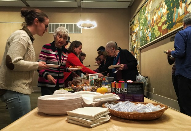 Attendees fill their plates with vegetarian food before discussing their hopes and fears.