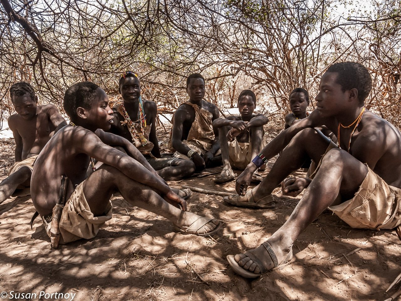 Hadzabe men sit in clearing in Tanzania
