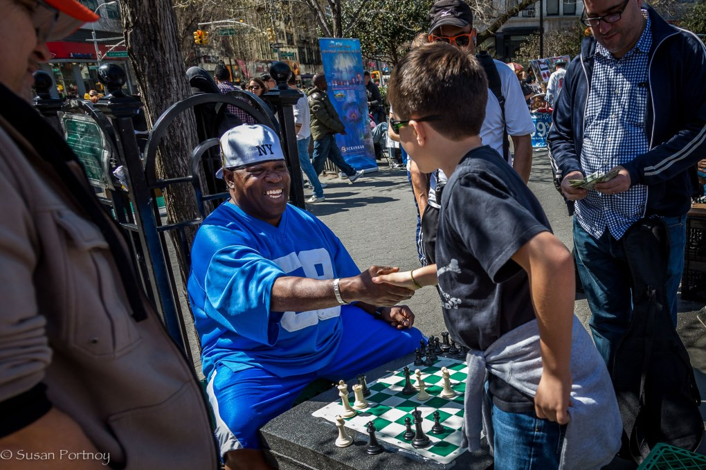 Man and boy congratulate each other after a game of chess in Union Square