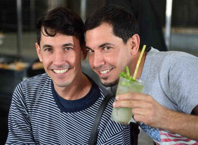 Cuban twin photographers Orlando and Eduardo Garcia (R-L) help the Sante Fe group get into the spirit over lunch at the Warehouse of Wood and Tobacco, a Cuban brewery.