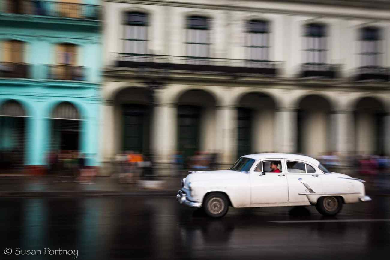 Panning shot of white classic car in Havana, Cuba