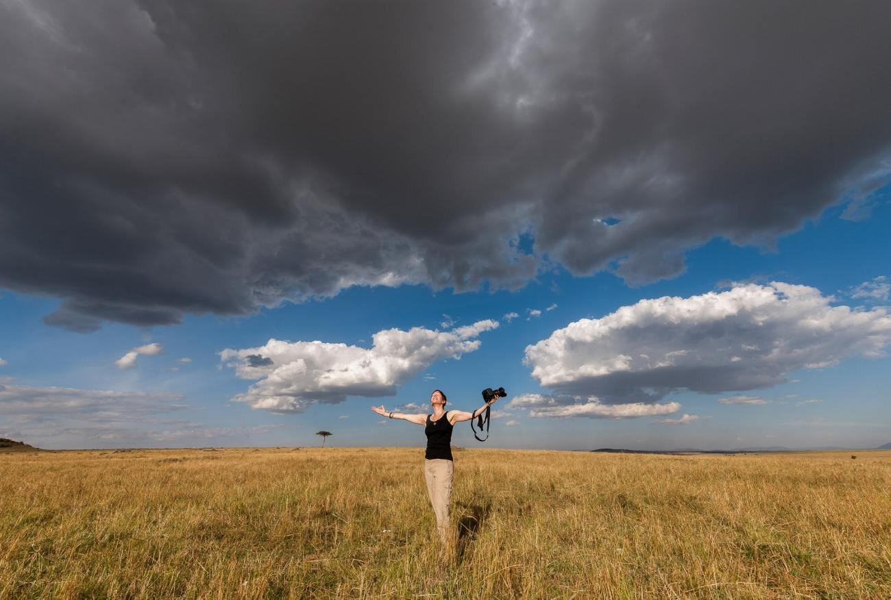 Susan Portnoy the Insatiable Traveler holding camera in the Masai Mara, Kenya