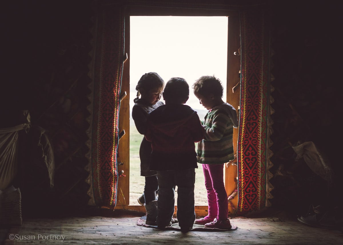 Three Kazakh children in the doorway of a ger