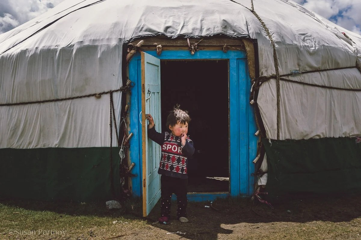 Toddler boy Kazakh at door of ger at Mongolia