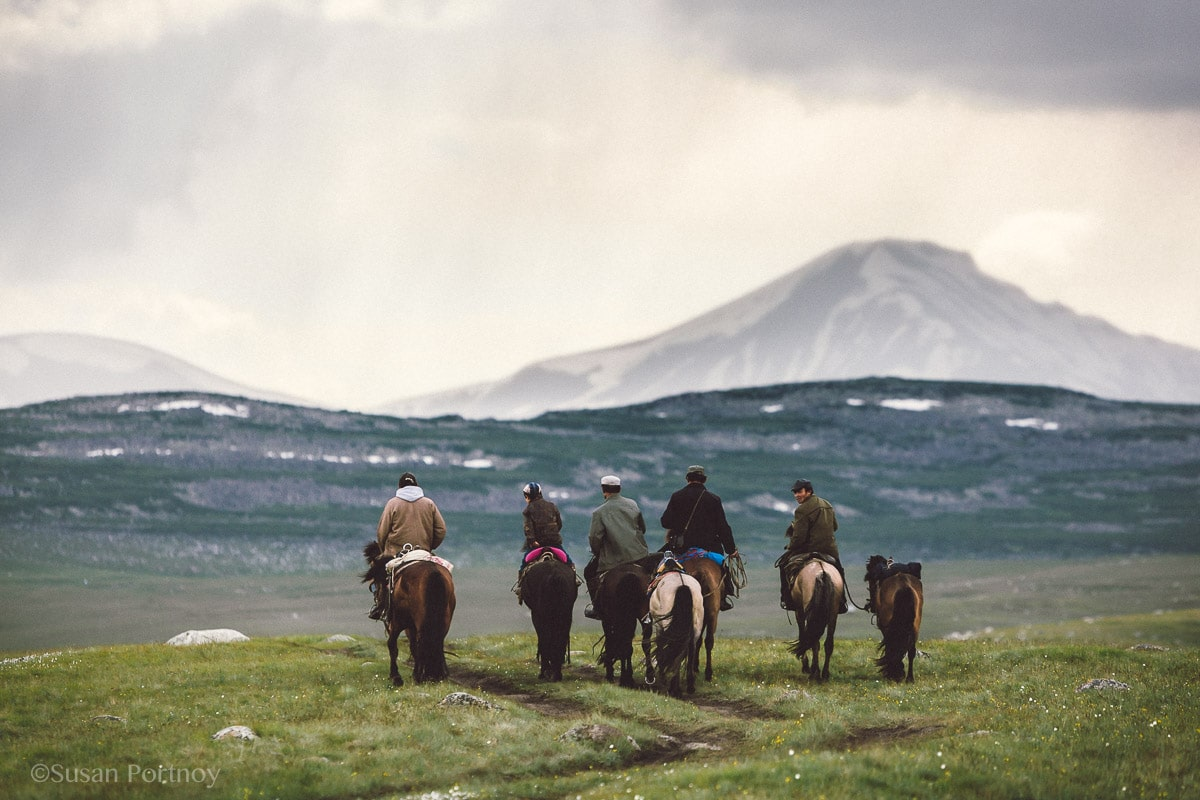 Men and children ride away from the camera in the altai mountains of Mongolia