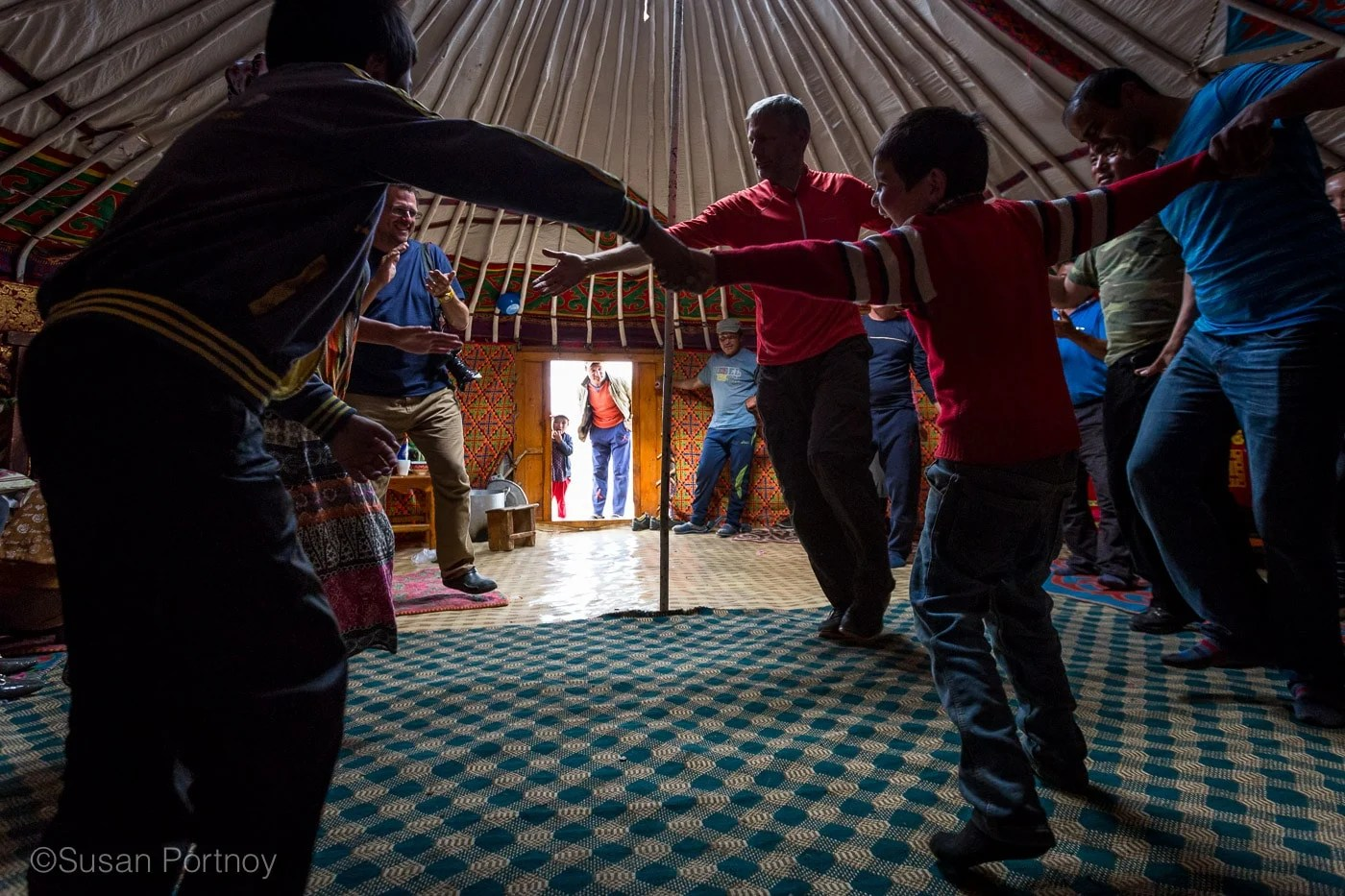 People holding hands and dancing in a circle at the Kazakh Mongolian Dance Party - The Insatiable Traveler