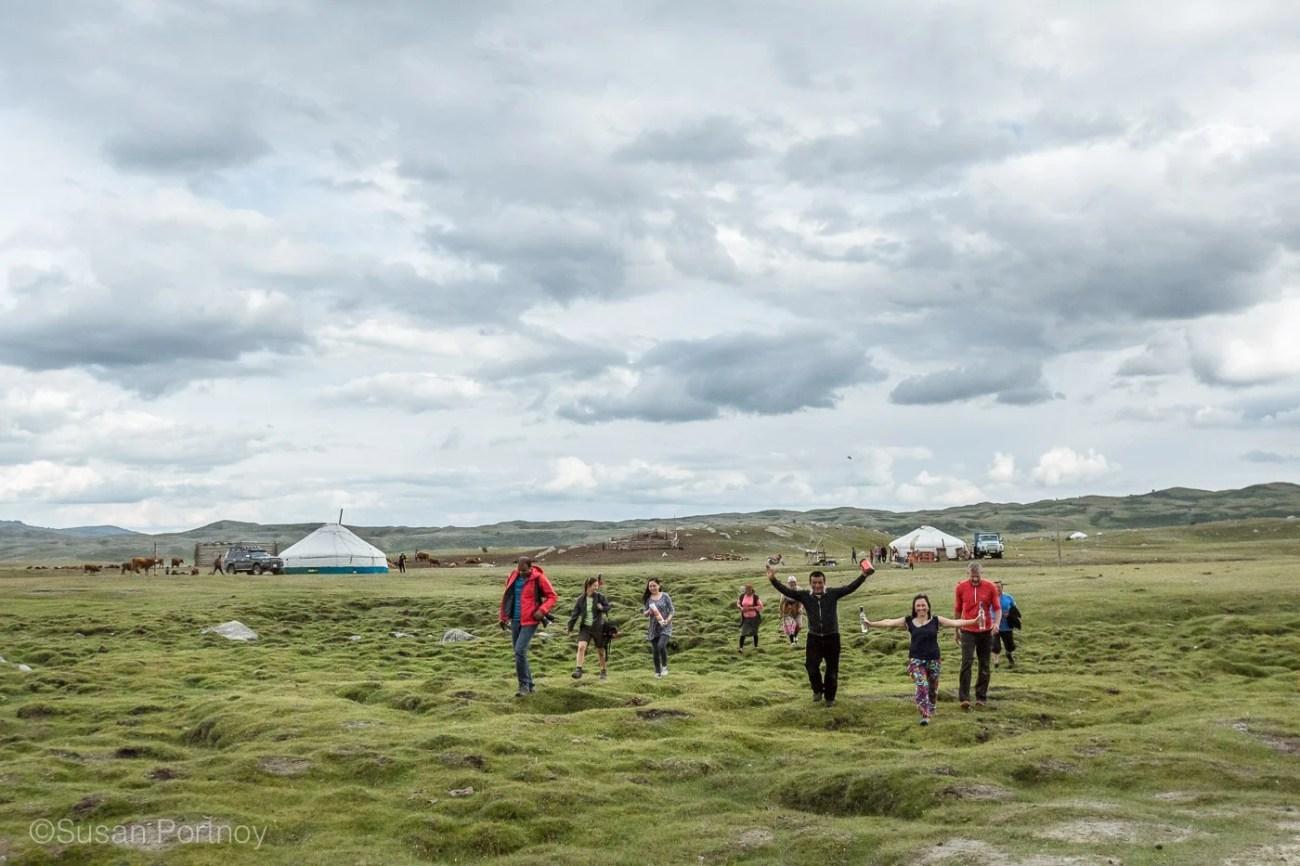 Kazakh's walking across a field during a Kazakh Mongolian Dance Party - The Insatiable Traveler