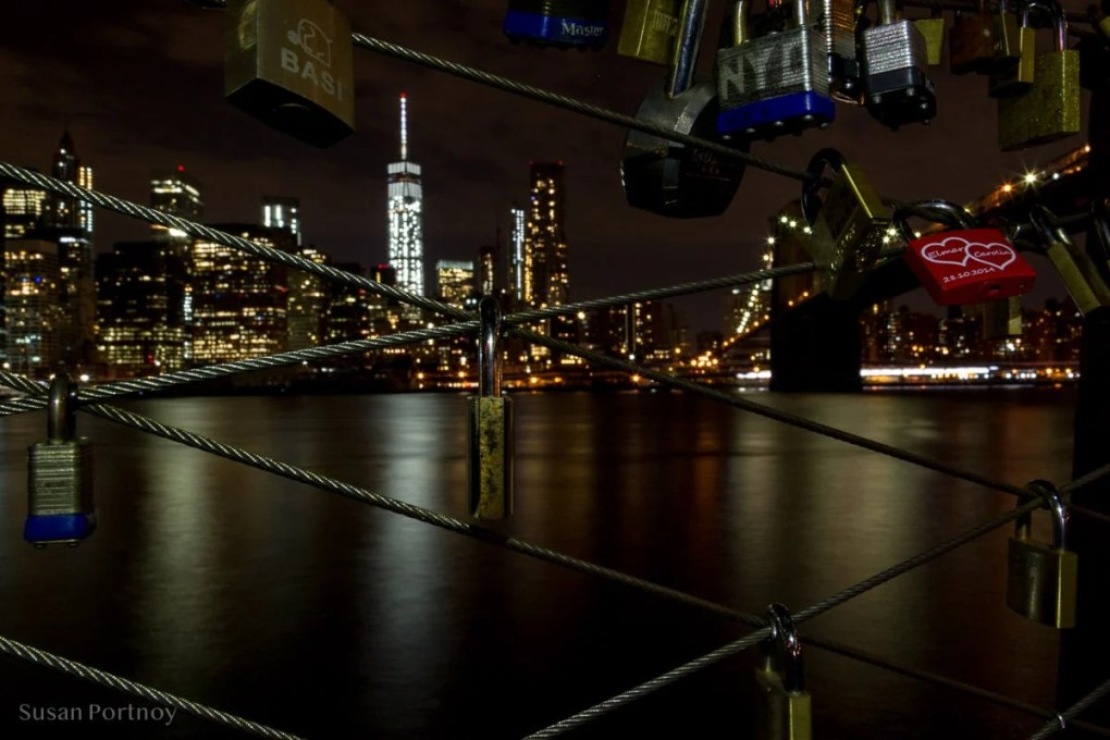 Close up of love locks on a fence at night with the World Trade Center WTC across the East River, New York City - Where to Photograph the Most Stunning Views of the New York Skyline at Night