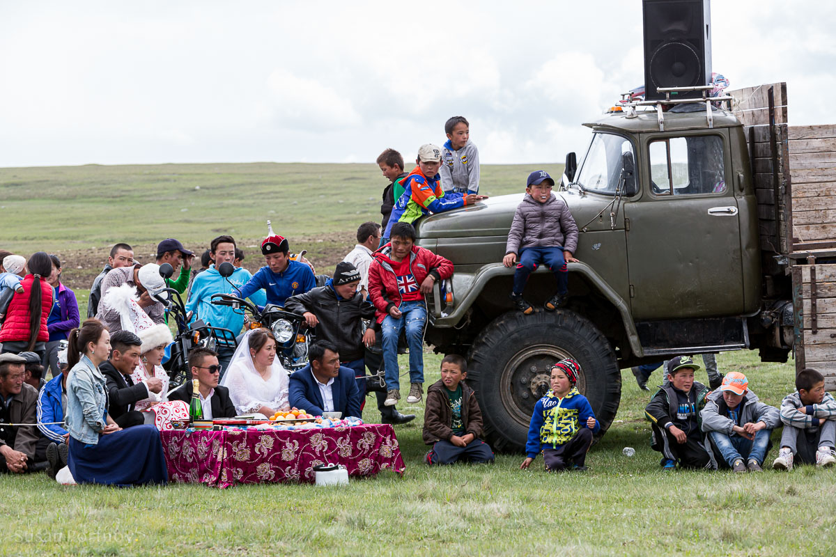 The wedding party sits on a makeshift dais at the end of the ring partly formed by guests and an old Russian flatbed truck where the AV equipment was stashed. They will drink fermented mare's milk which is one of many Kazakh traditions.