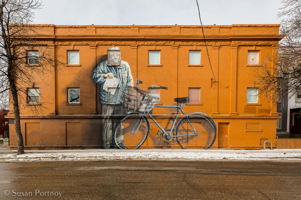 A giant mural of a man and an bicycle in Winnipeg - The Zoohky mural is one of dozens located in Winnipeg's West End neighborhood on the Eastern side of the building at 635 Sargent Avenue.