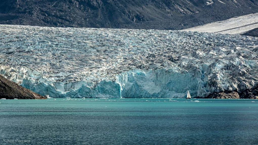 The massive glacier at the end of the Fjord of Eternity with a sailboat in front of it.