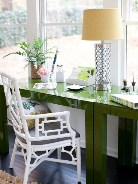 Pretty office with green desk and white rattan desk chair