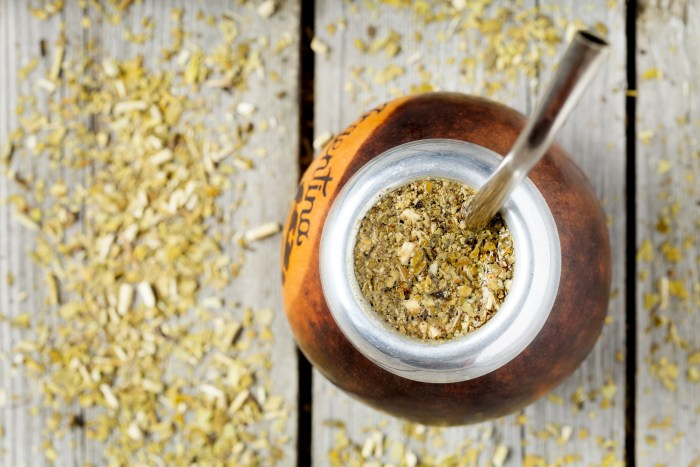 Traditional Argentina yerba mate tea beverage in calabash and bombilla in rustic style on vintage wooden background