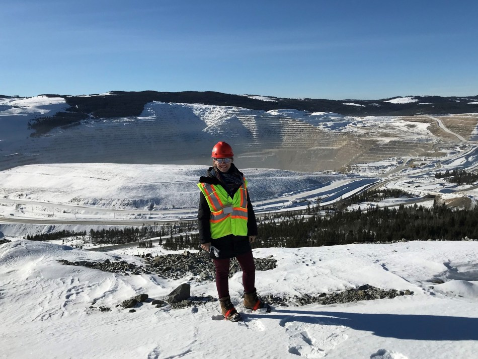 Elizabeth Freele stands smiling in front of a snowy open-pit mine. She is dressed in full PPE