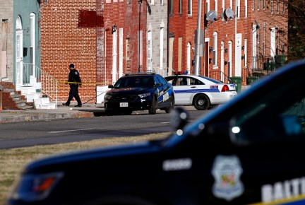 A member of the Baltimore Police Department walks behind a police line near the scene of the shooting death of Baltimore Police detective Sean Suiter in Baltimore, Friday, Nov. 17, 2017. The manhunt for Suiter's killer has entered its third day. Suiter was shot Wednesday in a particularly troubled area of West Baltimore while investigating a 2016 homicide and died Thursday. (AP Photo/Patrick Semansky)