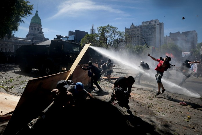 Protesters clash with police during a general strike against a pension reform measure, outside Congress in Buenos Aires, Argentina, Monday, Dec. 18, 2017. Union leaders complain the legislation, which already passed in the Senate, would cut pension and retirement payments as well as aid for some of poor families. (AP Photo/Victor R. Caivano)