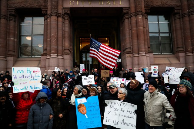 Demonstrators gather in solidarity against President Donald Trump's executive order temporarily banning immigrants from seven Muslim-majority countries from entering the U.S. and suspending the nation's refugee program Monday, Jan. 30, 2017, outside City Hall in Cincinnati. In addition, earlier in the day Mayor John Cranley declared Cincinnati a