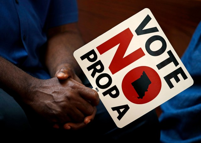 FILE - In this Tuesday, July 31, 2018, file photo, people opposing Proposition A listen to a speaker during a rally in Kansas City, Mo. Missouri votes Tuesday, Aug. 7 on a so-called right-to-work law, a voter referendum seeking to ban compulsory union fees in all private-sector workplaces. (AP Photo/Charlie Riedel, File)