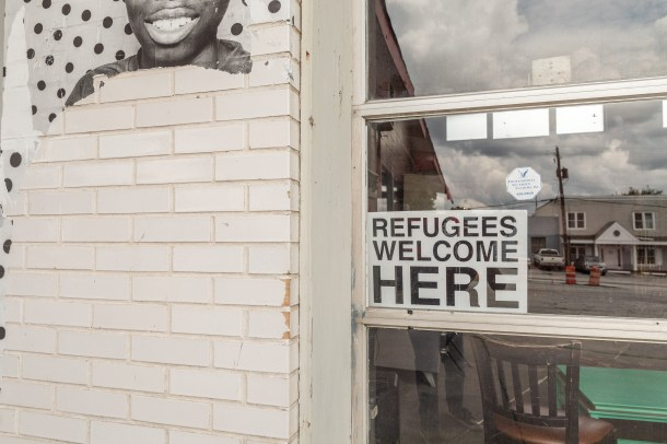 A sign welcoming refugees sits in a window at Refuge Coffee in Clarkston. Lynsey Weatherspoon for The Intercept