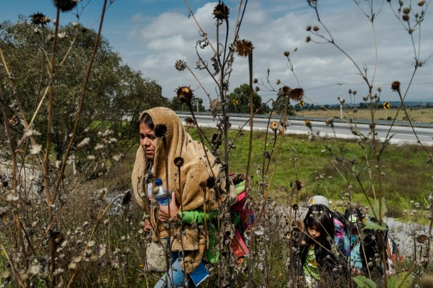 A Central American migrant woman walks up a hill near a truck rest stop after jumping off a cargo truck carrying migrants from the Central American caravan on its way to the city of Santiago de Querétaro on November 10, 2018. Earlier that morning thousands of migrants from the first caravan exited Mexico City where for over a week they rested and waited to continue their journey northbound to Tijuana.Photographer: Mark Abramson