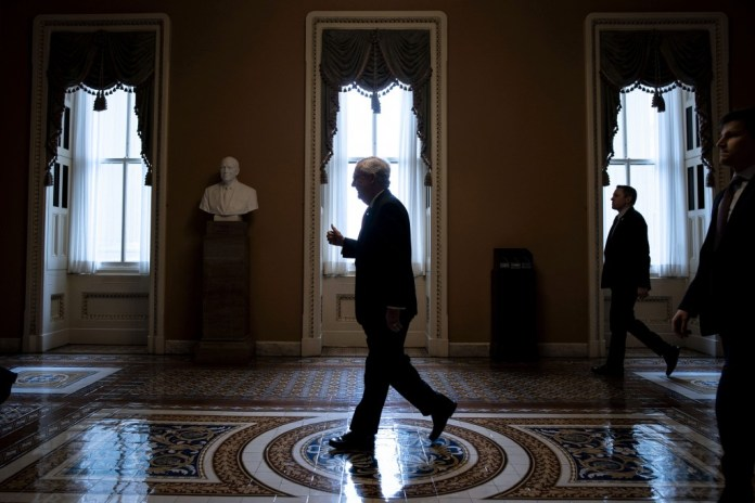 Senate Majority Leader Mitch McConnell, a Republican from Kentucky, gives a helping hand when he returns to his office after his opening remarks at the United States Capitol in Washington, DC, United States on Wednesday 25 March 2020. McConnell said the Senate was going to get together and pass this historic relief package today. Photographer: Al Drago / Bloomberg via Getty Images