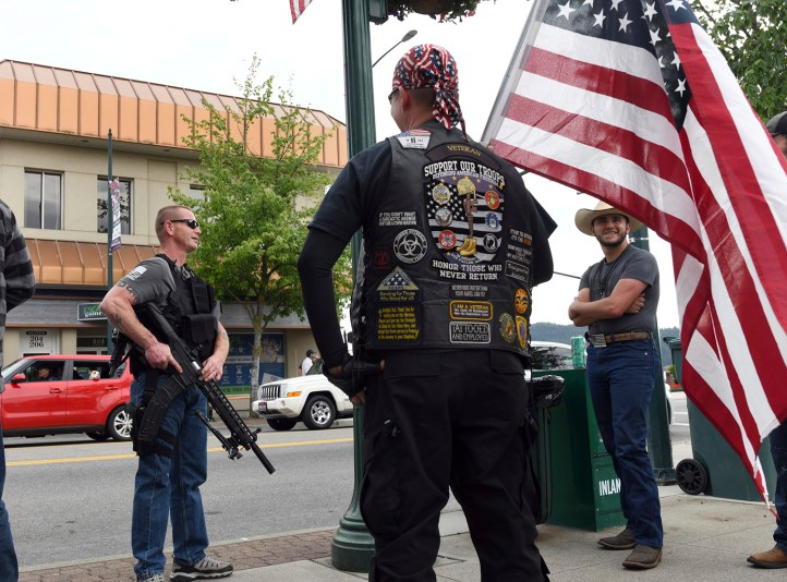 """""""We are not counter-protesters, we're just going to make sure Coeur d'Alene is safe"""" says Conrad Nelsen of Coeur d'Alene, Idaho, as he holds the flag while standing next to armed citizen Dan Carson, left, during a protest Tuesday, June 2, 2020, Coeur d'Alene, Idaho, about the killing of George Floyd.  (Kathy Plonka/The Spokesman-Review via AP)"""