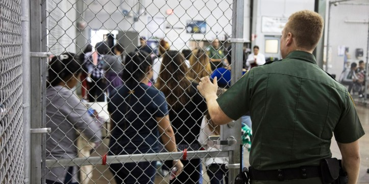 A U.S. Border Patrol agent watches as people who've been taken into custody.