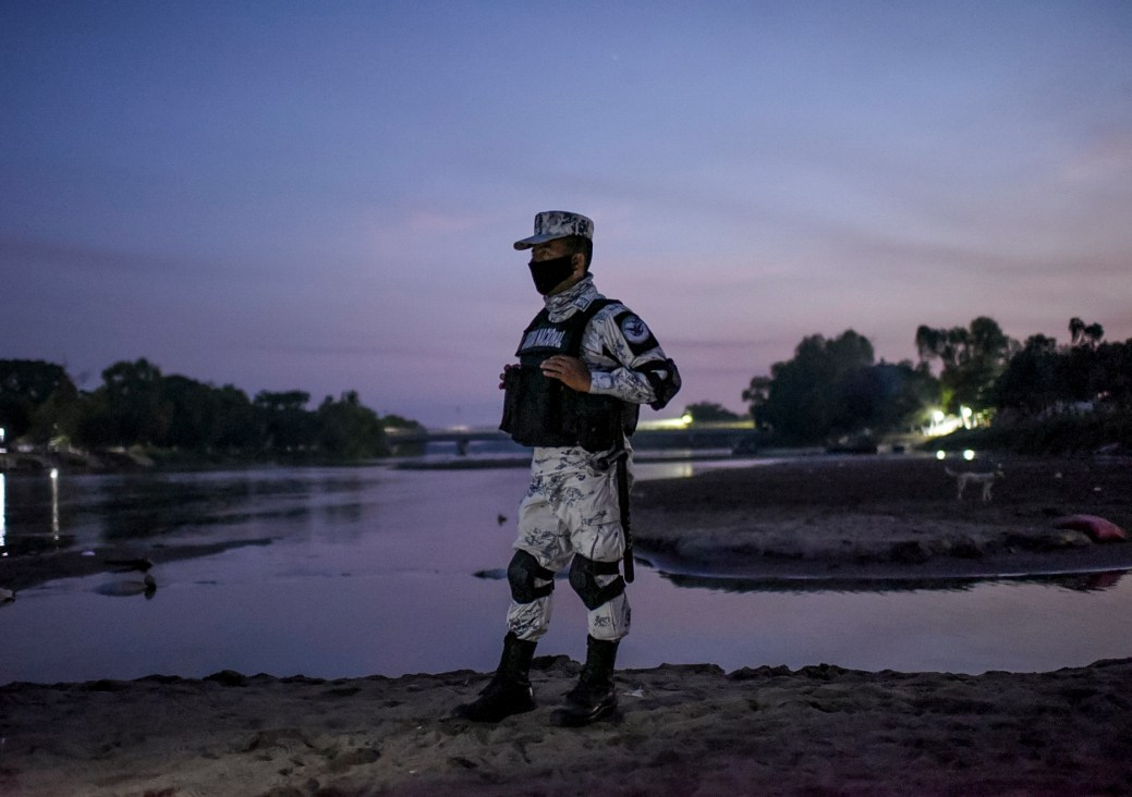 """TOPSHOT - An officer of the National Guard of Mexico stand guard at the banks of the Suchiate River in Ciudad Hidalgo, Chiapas state, Mexico, border with Tecun Uman, Guatemala, on January 19, 2021. - The Mexican government said it would not allow the """"illegal entry"""" of any migrant caravans and has deployed 500 immigration officers to the border states of Chiapas and Tabasco. (Photo by Isaac GUZMAN / AFP) (Photo by ISAAC GUZMAN/AFP via Getty Images)"""